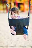 Happy 6-month-old baby girl in a swing by a park, ontario canada