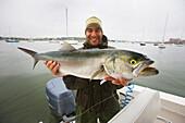 Man holding a striped bass, boston massachusetts usa