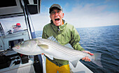 Excited man holding a striped bass, cape cod massachusetts usa