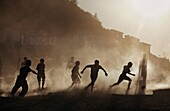 Silhouettes Of Mizo Boys Running On A Dusty Soccer Pitch At Sunset