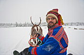 A Herder Wearing The Traditional Sami Clothing With Reindeer At Ounaskievari Reindeer Farm, Levi, Lapland, Finland