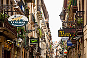 Narrow Street With Shop Signs In The Old Quarter, San Sebastian, Basque Country, Spain