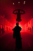 Silhouettes Of Monk With Banner Lit By Red Flare Walking Through Smokey Backstreets Of Lewes On Bonfire Night, East Sussex, Uk