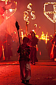Young Boy Dressed As A Smuggler With Torch On The United Grand Procession In Front Of Monks With Banners And Burning Crosses, Bonfire Night, Lewes, East Sussex, Uk