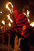 Young Boy Dressed As A Smuggler With Burning Torch On The United Grand Procession, Bonfire Night, Lewes, East Sussex, Uk