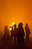 Silhouette Of People In Front Of Large Bonfire Watching Fireworks Display At Barcombe Bonfire Night, Barcombe, East Sussex, Uk