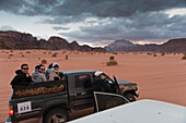 Tourists Sitting In The Back Of A 4X4 Vehicle Before Being Transported To A Captain's Eco Desert Camp, Wadi Rum, Jordan, Middle East