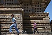 Two Boys Running In Front Of Ornate Carvings On Halebid Temple, Halebid, Karnataka, India