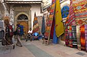 Backpackers Wander Through Carpet Market In Essaouira, Morocco