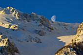 Moon standing above the snow-covered cirque at Monte Sirente, Valle Lupara, Monte Sirente, Abruzzi, Apennines, l' Aquila, Italy