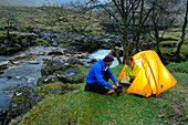 Couple cooking infront of a tent, Glen Etive, Buachaille Etive Mor, Highlands, Scotland, United Kingdom