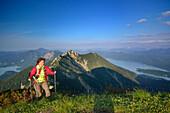 Female hiker ascending to Heimgarten, lake Kochelsee, Benediktenwand, Jochberg, Herzogstand and lake Walchensee in background, Upper Bavaria, Bavaria, Germany