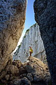 Woman standing on boulder in canyon Kaisersaele, Kampenwand, Chiemgau Alps, Chiemgau, Upper Bavaria, Bavaria, Germany
