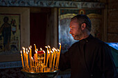 Priest with offering candles inside the Church of the Intercession of the Virgin at Kizhi Pogost, Kizhi Island, Lake Onega, Russia, Europe