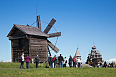 People in front of wooden windmill, belfry and Church of the Intercession of the Virgin and Church of the Transfiguration at Kizhi Pogost in distance, Kizhi Island, Lake Onega, Russia, Europe