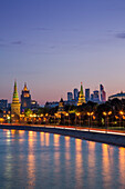 Moskva river and illuminated Kremlin buildings at dusk with Moscow City skyscrapers in the distance, Moscow, Russia, Europe