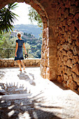 Barefoot passing an archway, Deia, Majorca, Spain