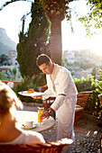 Waiter serving a drink on a terrace of a bistro, Deia, Majorca, Spain