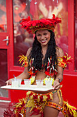 Cheerful woman serving drinks at Miscigenacao dance and folklore show with Boi Bumba festival costumes, Parintins, Amazonas, Brazil