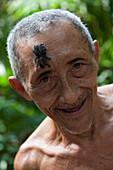 Indigenous man living in the Amazon rainforest with baby tarantula on his forehead, on Boa Vista do Acaro island, near Belem, Para, Brazil