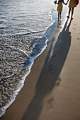 Mother and daughter strolling along Playa Las Hamacas beach, Acapulco, Guerrero, Mexico