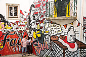 Couple kissing in front of a graffiti mural on the wall of steps linking the Baixa and Alfama district, Lisbon, Lisboa, Portugal