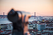 Coin-operated telescope at Castelo de San Jorge, St. George's Castle, in the Alfama district with view over the city and Ponte 25 de Abril bridge over Tagus river at sunset, Lisbon, Lisboa, Portugal