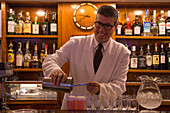 Friendly barkeeper mixing delicious Bellini drinks in Harry's Bar, Venice, Veneto, Italy, Europe
