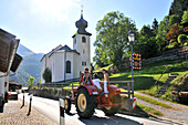 Tractor driving through Wall in the Inn valley, Bavaria, Germany