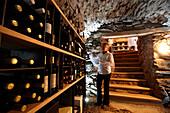 Frau nimmt Wein aus Regal in einem Weinkeller, Karthaus, Schnalstal, Südtirol, Alto Adige, Italien