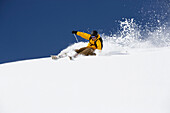 Man downhill skiing in deep snow, Grisons, Switzerland