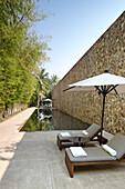 Sunlounger beside lap pool, Amansara Hotel, Siem Reap, Cambodia