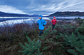 Young couple jogging along Loch Maree, Northwest Highlands in background, Scotland, United Kingdom