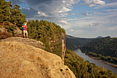 Young woman enjoying view over river Elbe, Saxon Switzerland National Park, Saxony, Germany
