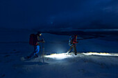 Young couple hiking across snowy Highlands, Wester Ross, Torridon, Scotland, United Kingdom