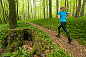 Young woman jogging through a beech forest, National Park Hainich, Thuringia, Germany