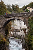 Young woman with backpack passing a bridge over the Mera river, Promontogno, Bergell, Canton of Grisons, Switzerland