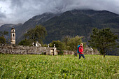Young woman with backpack hiking, Soglio, Bergell, Canton of Grisons, Switzerland