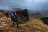 Young woman hiking in rain, Quiraing, Trotternish peninsula, Isle of Skye, Scotland, United Kingdom