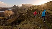 Young couple running on a trail, Quiraing, Trotternish peninsula, Isle of Skye, Scotland, United Kingdom