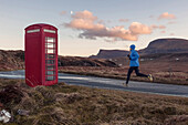 Young man jogging, passing a red booth, Isle of Skye, Trotternish Peninsula, Scotland, United Kingdom