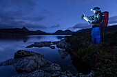 Young man with headlamp reading a hiking map at Loch Bad a Ghaill at dusk, Stac Pollaidh, Cul Beag, Sgorr Tuath and Ben Mor Coigach in background, Assynt, Scotland, United Kingdom