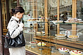 Woman looking at a shop window of a patisserie, Corso Magenta, Milan, Lombardy, Italy