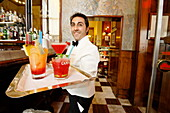 Waiter serving several drinks in a bar, Galleria Vittorio Emanuele II, Milan, Lombardy, Italy