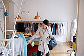 Woman shopping in a fashion boutique, Navigli, Milan, Lombardy, Italy
