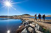 Three hikers passing Pretty Valley Pondage, Alpine National Park, Australian Alps, Victoria, Australia