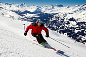 Skier downhill skiing from mount Parpaner Rothorn, Lenzerheide, Canton of Graubuenden, Switzerland