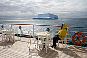 Woman relaxing on the deck of cruise ship MS Deutschland (Reederei Peter Deilmann) as vessel passes the Antarctic icebergs, near King George Island, South Shetland Islands, Antarctica