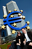 Couple eating ice cream by the Euro monument and the European Central Bank, Frankfurt, Germany