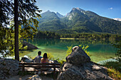 Young couple sitting on a bench at Hintersee, view to Hochkalter, near Ramsau, Berchtesgaden region, Berchtesgaden National Park, Upper Bavaria, Germany